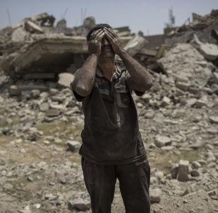 رجل يبكي أمام جثة ابنته في الموصل، العراق 8 يوليو/ تموز 2017