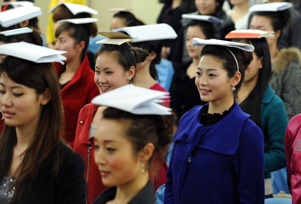 فتيات يافعات خلال التدريب على الوقوف والابتسامة قبل الوصول إلى المرحلة الأخيرة لاختيارهن في طاقم مضيفات طيران الخطوط الجوية الصينية