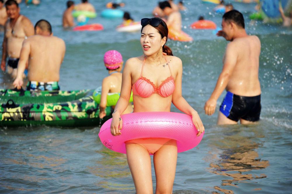 فتاة على شاطئ تشينغداو، الصين 22 يوليو/ تموز 2017