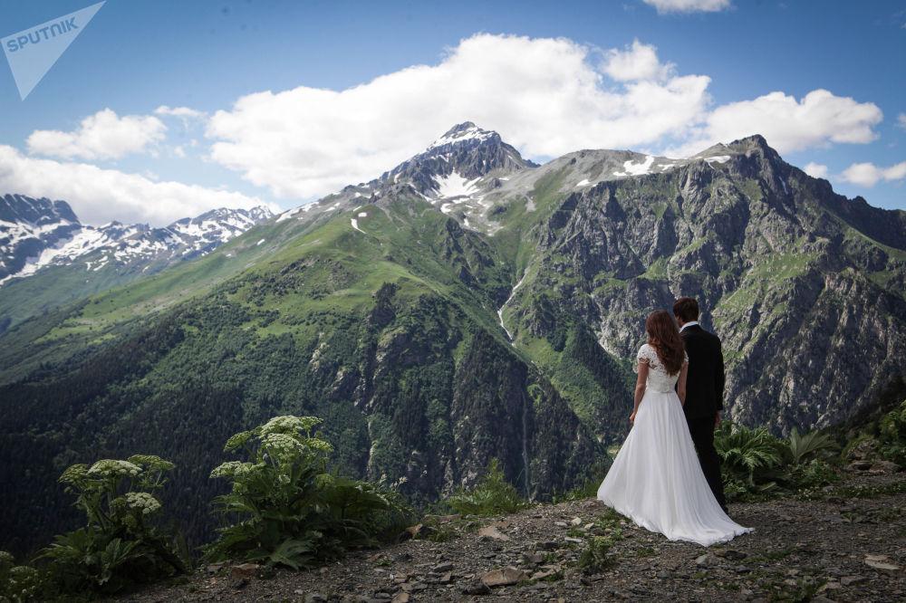 متزوجان حديثا على خلفية منتجع دومباي الجبلي في قراتشاي - تشيركيسيا شمال القوقاز، روسيا الاتحادية