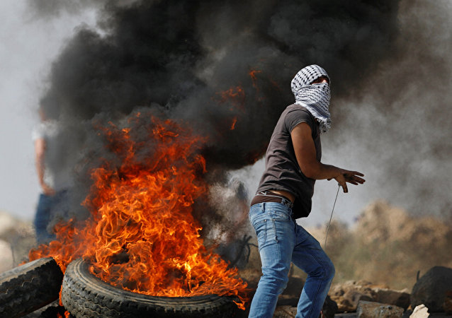 فلسطينيون ملثمون بجانب الإطارات المحترقة خلال اشتباكات مع القوات الإسرائيلية فى قرية الخبر بالضفة الغربية بالقرب من رام الله
