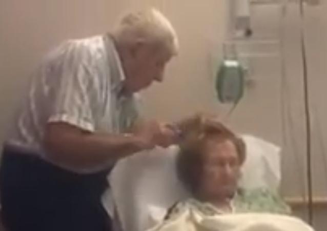عجوز يسرح شعر زوجته المسنة وهي على فراش الموت