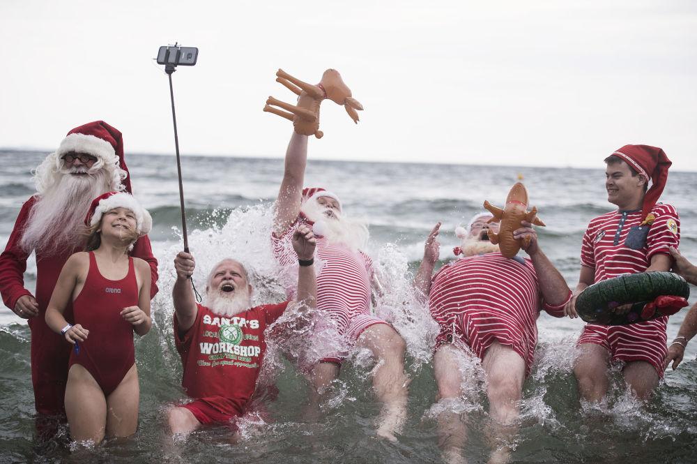 قفزة سانتا خلال التقاط صورة جماعية في الماء في متنزه ديريافسباكن في كلامبنبورغ، شمال كوبنهاغن في 25 يوليو/ تموز 2017
