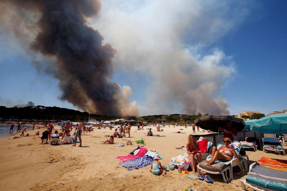 سياح على خلفية دخان يتصاعد خلف الشاطئ في بورمس-لي-ميموساس، فرنسا 26 يوليو/ تموز 2017