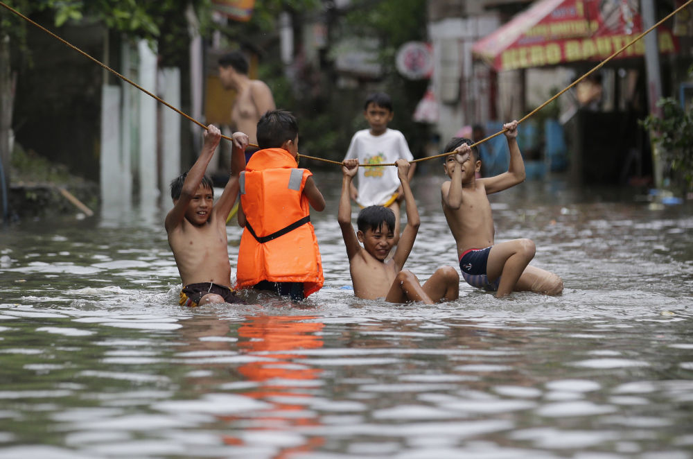 فتيان يلعبون خارج منازلهم المغمورة إثر الأمطار الغزيرة التي سببتها العاصفة الاستوائية نيسات أجزاء من مانيلا الكبرى، الفلبين 27 يوليو/ تموز 2017