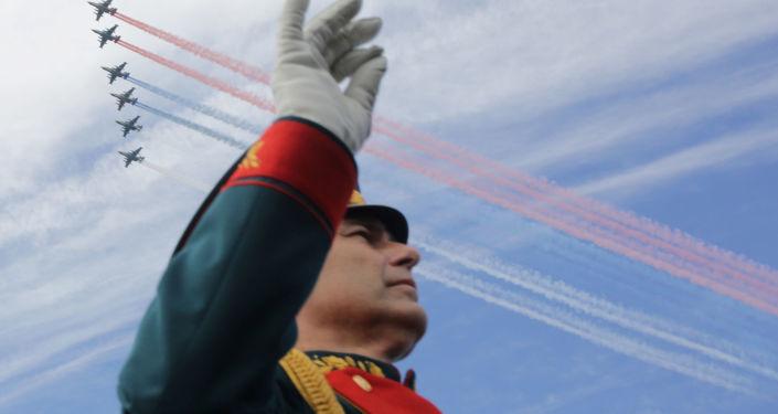 موسيقار لفرقة موسيقية عسكرية على خلفية طائرات حربية روسية ترسم ألوان علم روسيا في سماء مدينة سان بطرسبورغ، روسيا