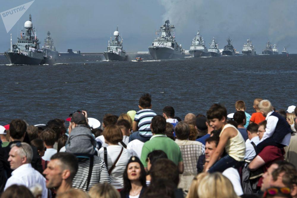 الجمهور على خلفية سفن حربية مشاركة في العرض العسكري البحري احتفالا بيوم القوات البحرية الروسية في كرانشتد، روسيا