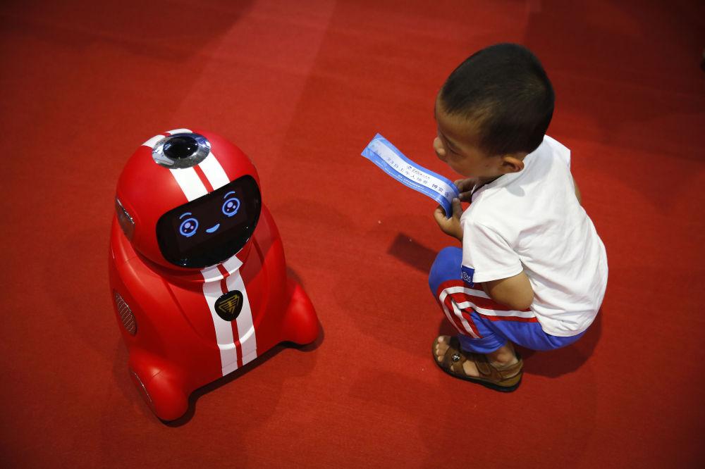 طفل يحمل تذكرة دخول ينظر إلى رجل آلي (يتميز بالتعلم الذاتي) خلال المؤتمر الدولي للرجال الآلية في ييتشوانغ في بكين،  23 أغسطس/ آب 2017