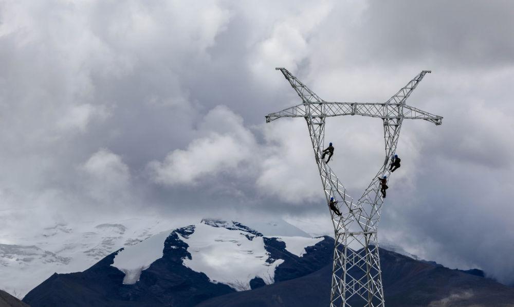 مهندسون يعملون على أعمدة الكهرباء في جبال شان نان، الصين 19 أغسطس/ آب 2017
