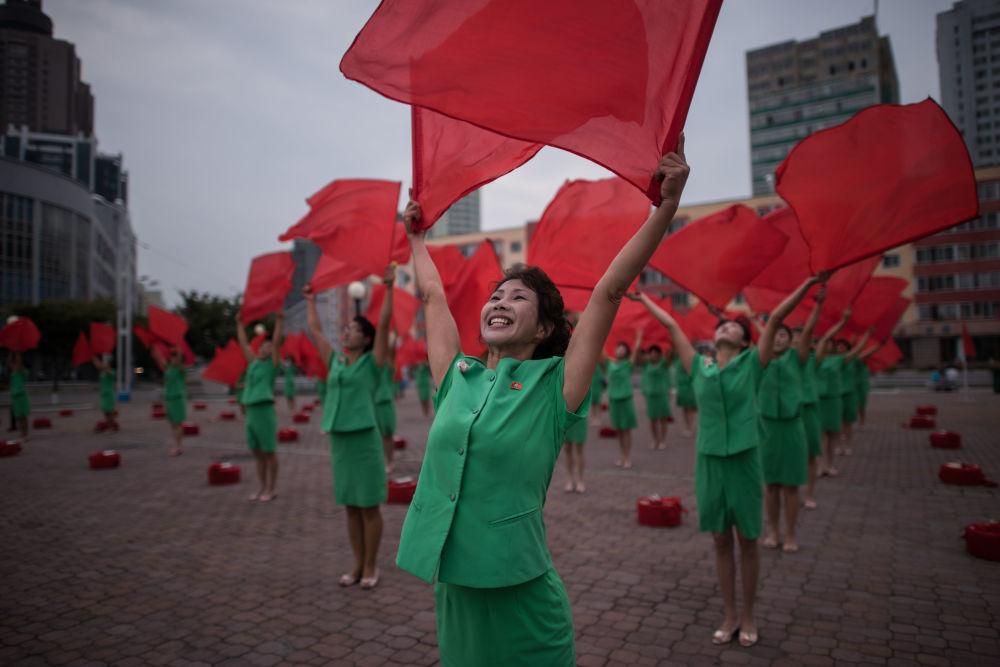 فرقة  دعائية تقوم بإجراء روتيني للتلويوح بالأعلام خارج محطة السكة الحديدية المركزية فى بيونغ يانغ، كوريا الشمالية 27 سبتمبر/ أيلول 2017