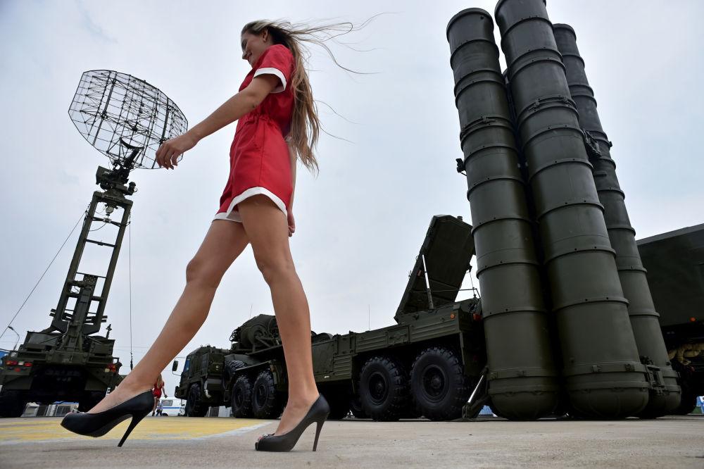 فتاة تسير على خلفية منظومة الدفاع الجوي إس-400 (تريومف) في المعرض العسكري أوبورون إكسبو-2014 في مدينة جوكوفسكي، روسيا