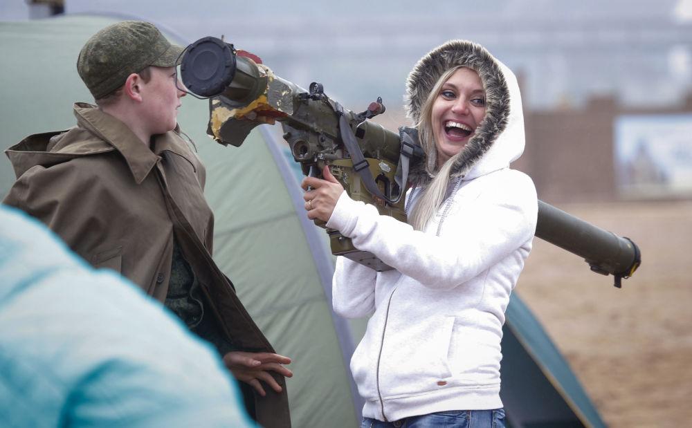 فتاة تحمل منظومة الدفاع الجوي المحمولة إيغلا في المعرض العسكري في سان بطرسبورغ، روسيا