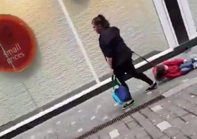 سيدة تسحب طفلا في ليفربول