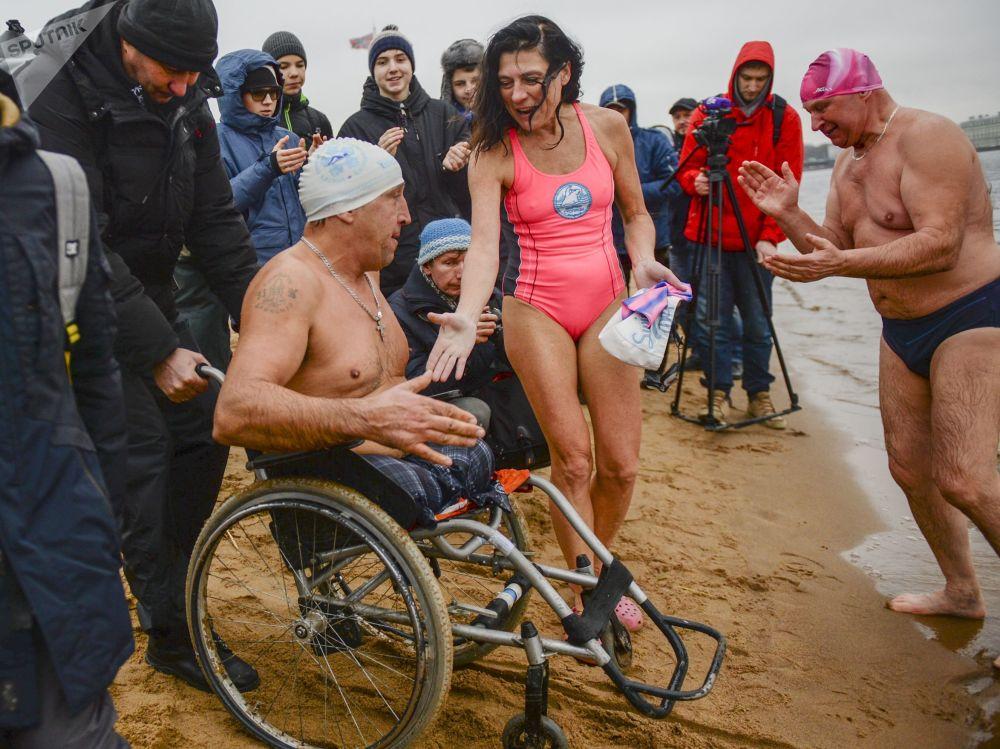 المشاركون في مهرجان السباحة الشتوية ليدوستاف على ضفة نهر نيفا أمام قلعة بطرس وبولس في سان بطرسبورغ، روسيا