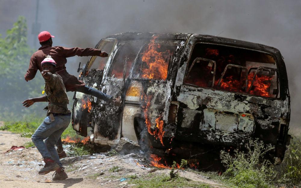 مؤيدون لحركة المعارضة الكينية التحالف الفائق الوطني بالقرب من السيارة المحترقة في إمباكاسي، كينيا