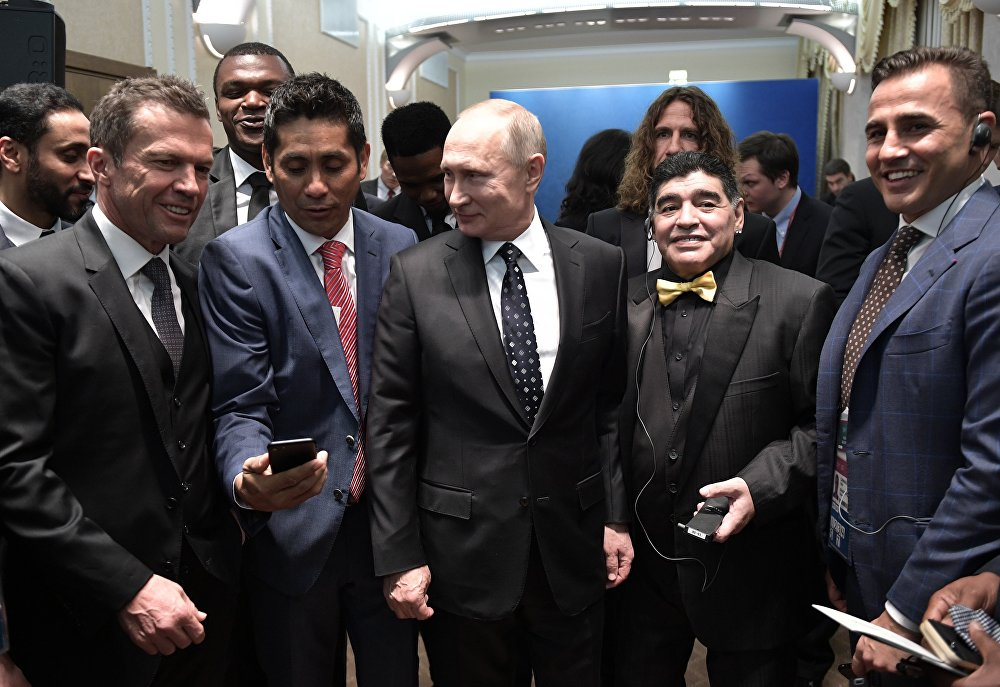 الرئيس الروسي فلاديمير بوتين مع نجوم الكرة العالمية، من اليمين  الإيطالي فابيو كانافارو، الأرجنتيني دييغو مارادونا، الألماني لوثر ماتيوس
