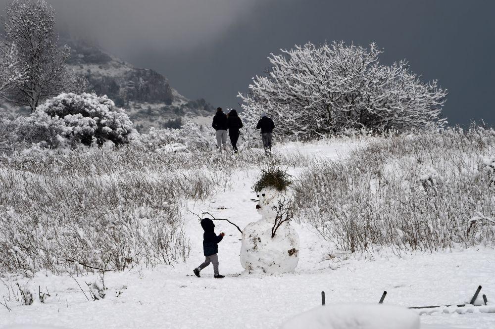 طفل يلعب بالقرب من رجل الثلج في مارسيليا، فرنسا 2 ديسمبر/ كانون الأول 2017