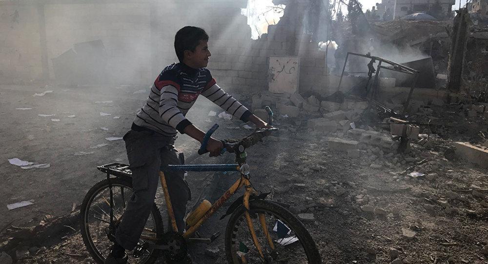 طفل بجانب مبنى مدمر في قطاع غزة