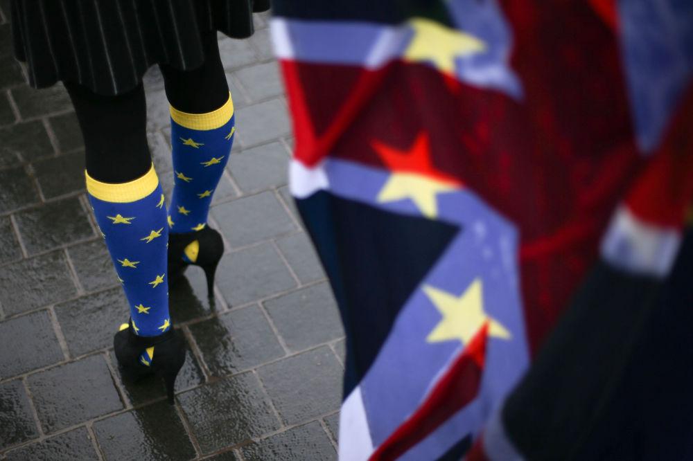 مشاركة في مظاهرة مناهضة للخروج من الاتحاد الأوروبي، ترتدي جوارب مزخرفة بنجوم الاتحاد الأوروبي، على خلفية علم بريطانيا، خارج البرلمان البريطاني، في وسط لندن في 13 ديسمبر/ كانون الأول 2017