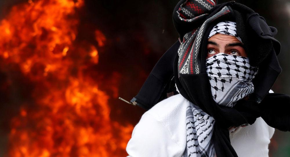 متظاهر فلسطيني ضد قرار الرئيس دونالد ترامب بإعلان مدينة القدس عاصمة لإسرائيل، بالقرب من حاجز قلنديا بالقرب من رام الله، الضفة الغربية، فلسطين 20 ديسمبر/ كانون الأول 2017