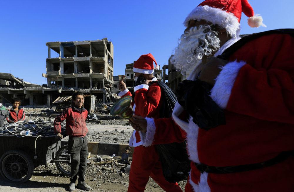 أطفال سوريون يبتسمون لرجال سانتا كلاوز (بابا نويل) في الرقة، سوريا 26 ديسمبر/ كانون الأول 2017