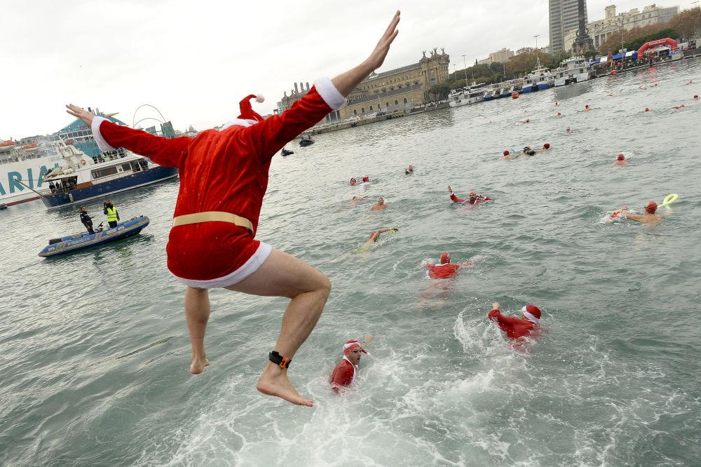 مشارك في زي سانتا كلاوز يقفز إلى مياه ميناء برشلونة، ضمن مسابقة كوبا نادال (كأس الميلاد) في إسبانيا، 25 ديسمبر/ كانون الأول 2017
