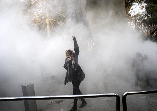 طالبة جامعية في مظاهرة داخل جامعة طهران وقت إلقاء قنبلة دخان من قبل الشرطة الإيرانية لمكافحة الشغب