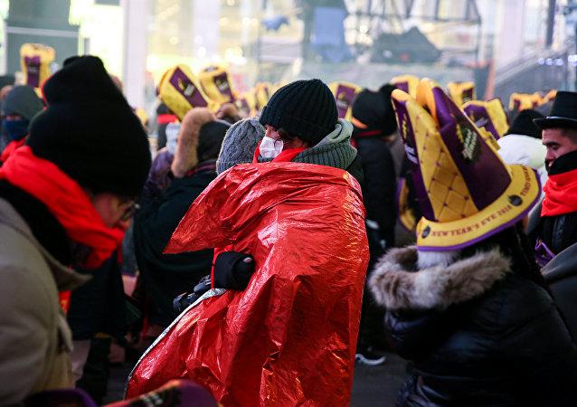 وافدون يشعرون بالصقيع نتيجة درجات الحرارة الباردة في تايمز سكوير قبيل احتفالات رأس السنة الجديدة في نيويورك 31 ديسمبر/كانون الأول 2017