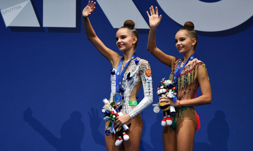لاعبتا الجمباز الروسيتان دينا أفيرينا (الفضة) وأرينا أفيرينا (الذهب) خلال مرام توزيع الجوائز في بطولة العالم لألعاب الجمباز في بيزارو، إيطاليا