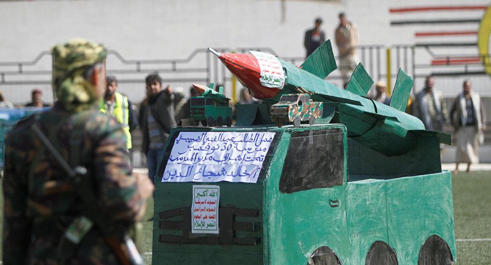 جندي من أنصار الله يقف أمام نموذج كرتون لصاروخ خلال تجمع بمناسبة 1000 يوم من التدخل العسكري بقيادة السعودية في الصراع اليمني