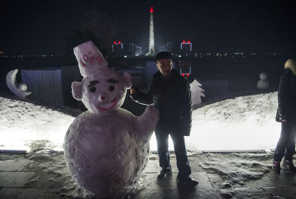 طفل بجانب رجل الثلج في العاصمة الكورية الشمالية بيونغ يانغ