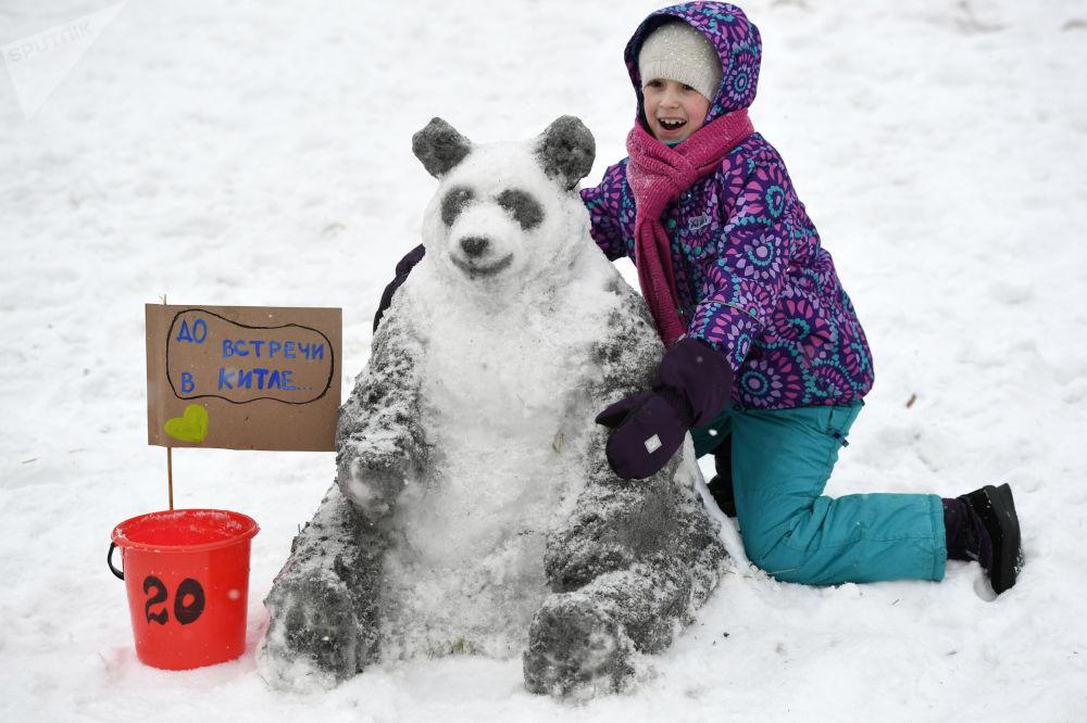 طفلة بجانب رجل ثلج الباندا في مسابقة الفنون في موسكو