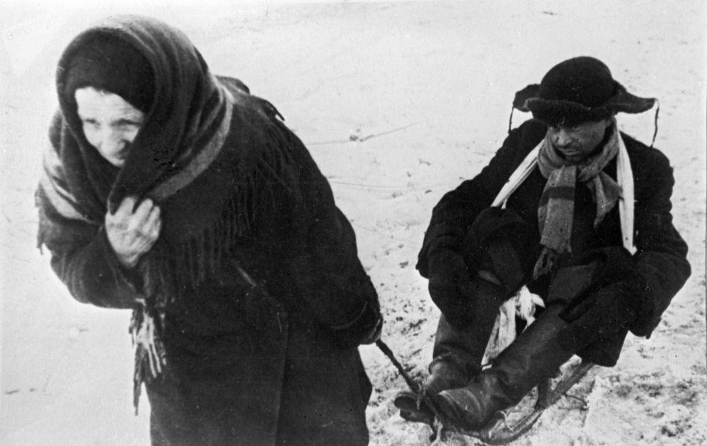 امرأة تجر زوجها الذي أصبح هزيلا جراء مجاعة لينينغراد، خلال حصار المدينة