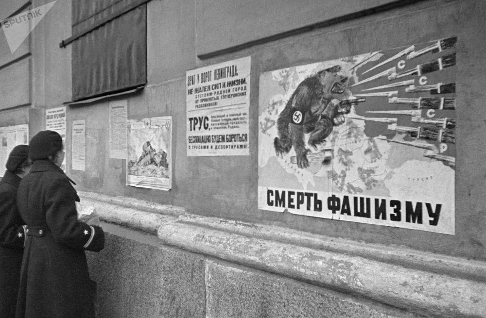 فتيات يقرأن منشورات ملصقة على جدار منزل، أكتوبر/ تشرين الأول 1941