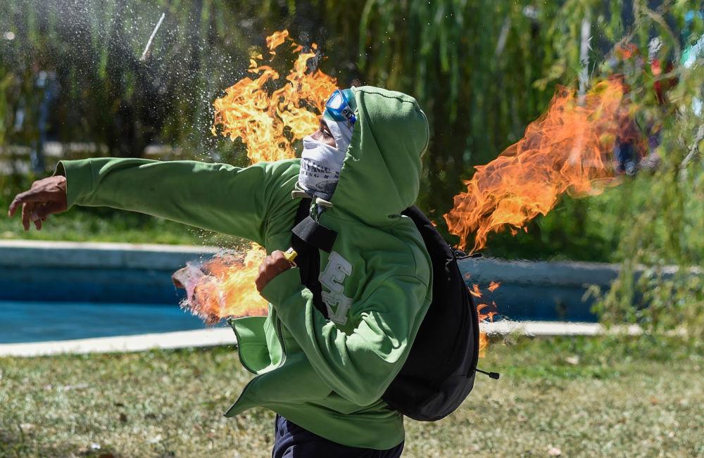 متظاهر يقذفبـ كوكتيل مولوتوف  تجاه الشرطة خلال الاشتباكات في كراكاس، فنزويلا  22 يناير/ كانون الثاني 2018