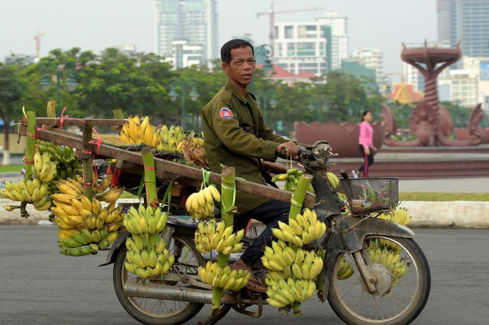 رجل كمبودي يركب دراجة نارية محملة بالموز في شارع بمدينة بنوم بنه، كومبوديا 23 يناير/ كانون الثاني 2018
