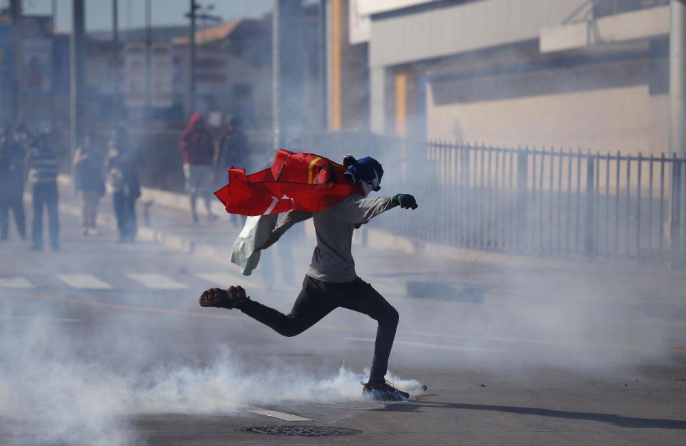 متظاهر يحاول قذف قنبلة غازية بعيدا خلال الاشتباكات بين الشرطة والمتظاهرين، وذلك أثناء تنصيب خوان أورلاندو رئيسا لهندوراس، 27 يناير/ كانون الثاني 2018