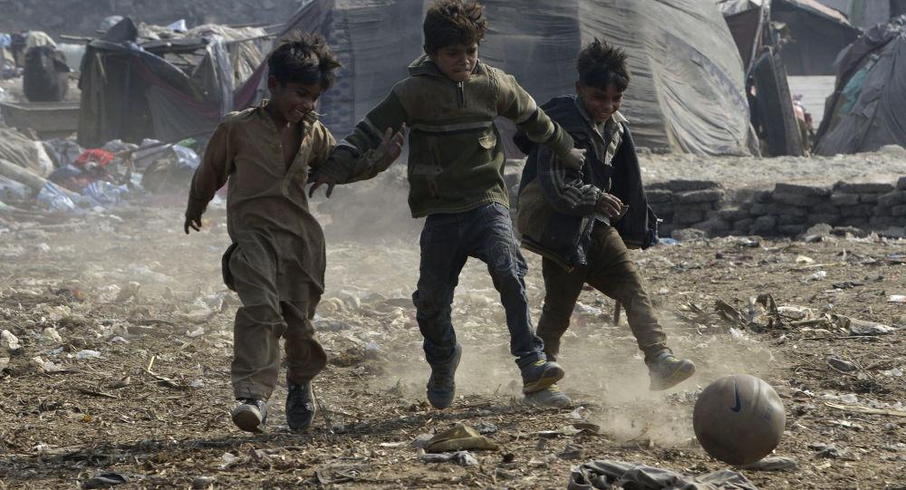 أطفال باكستانيون يلعبون بالكرة في لاهور، باكستان 30 يناير/ كانون الثاني 2018