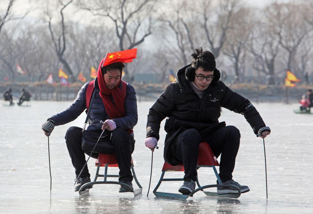 سياح يركبون زلاجات على جليد بحيرة كونمين  في ضواحي بكين، الصين