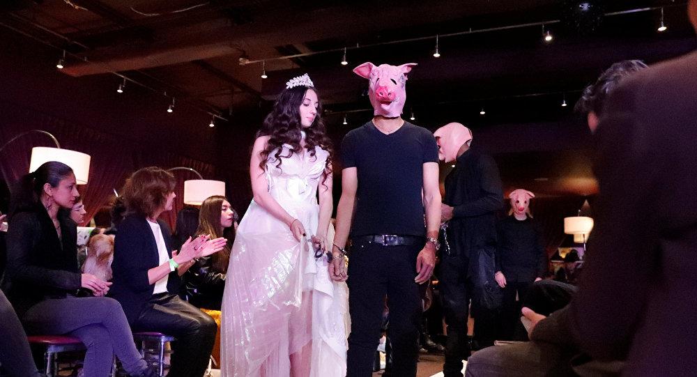 عارضة أزياء بأجنحة ملائكة وعارض أزياء بوجه خنزير خلال عرض الأزياء الذي أقيم في 9 فبراير/شباط 2018 في مدينة نيويورك الأمريكية لمناهضة التحرش الجنسي
