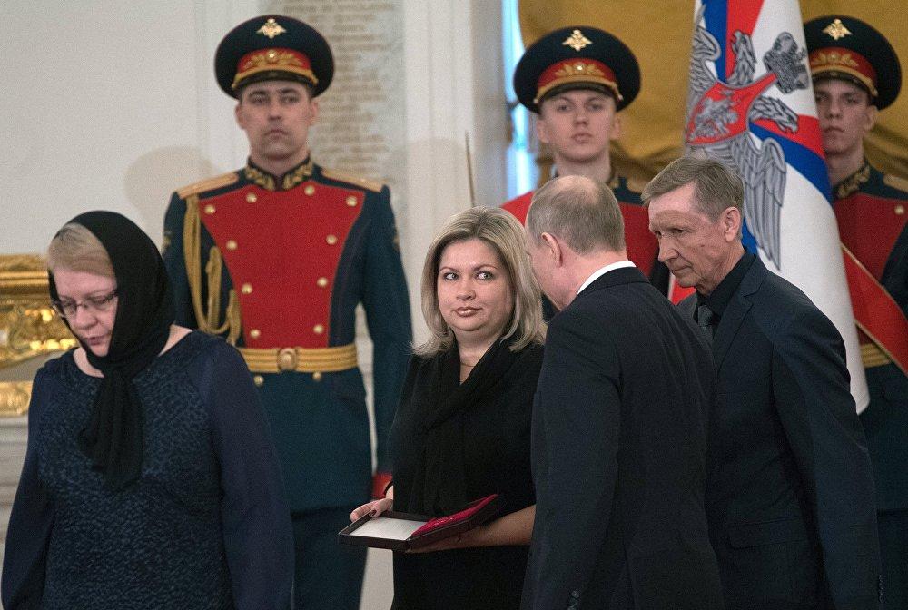 بوتين  يقدم  في وسام النجمة الذهبية إلى عائلة الرائد الطيار رومان فيليبوف في 23 فبراير/شباط 2018