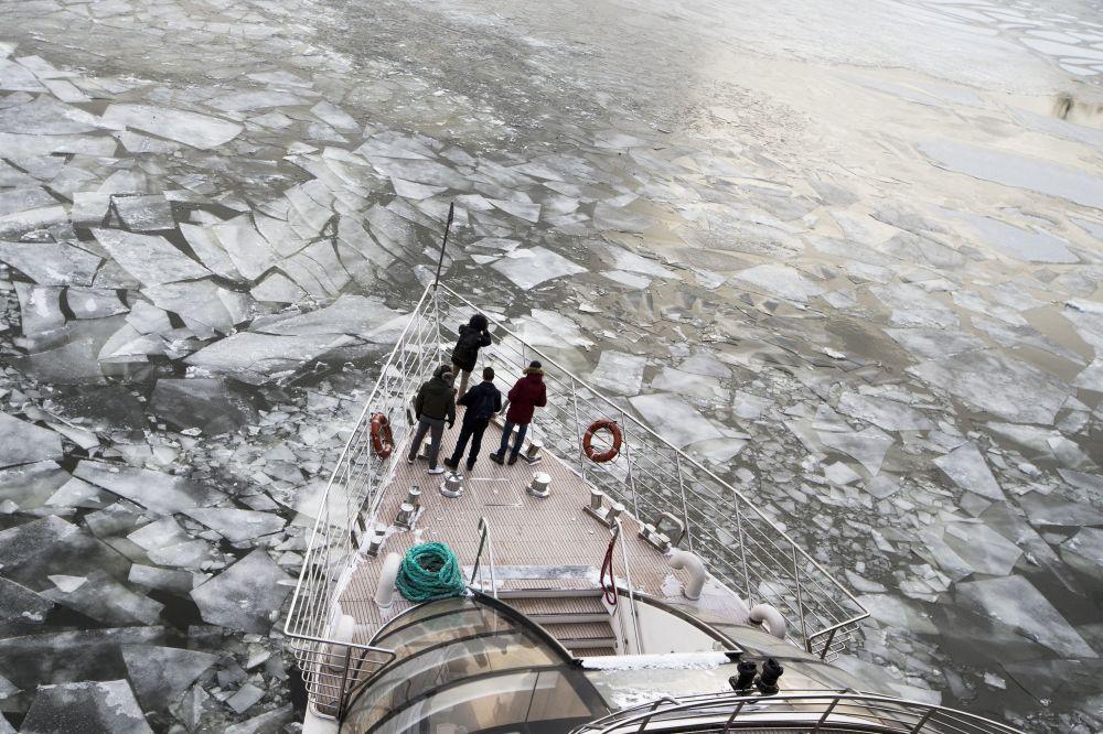 ركاب يقفون على متن زورق سياحي على نهر موسكو المغطى بالجليد في موسكو، 26 فبراير/ شباط 2018