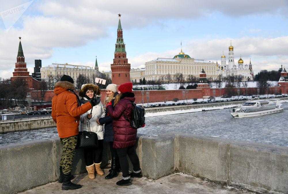 مواطنون على جسر بولشوي كاميني يلتقطون صورة سيلفي على خلفية نهر موسكو المغطى بالجليد