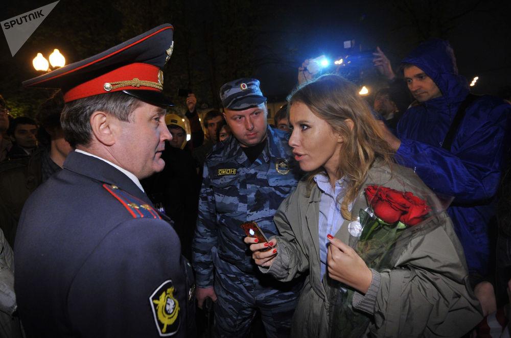 مقدمة البرامج التلفزيونية كسينيا سوبتشياك تتحدث إلى شرطي خلال مسيرة للمعارضة في ساحة كودرينسكايا في موسكو