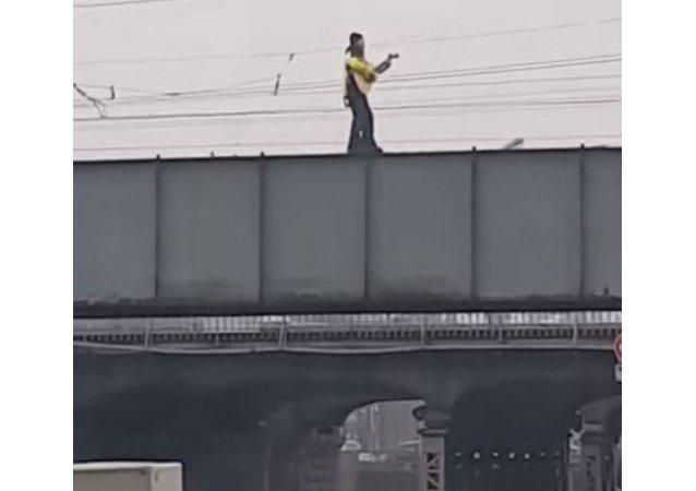 رجل يتزلج على جسر وهو يعزف على الغيتار