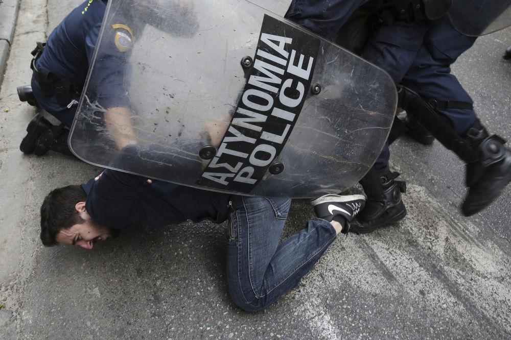 شرطة الشغب تلقي القبض على أحد المتظاهرين في أثينا، اليونان 14 مارس/ آذار 2018