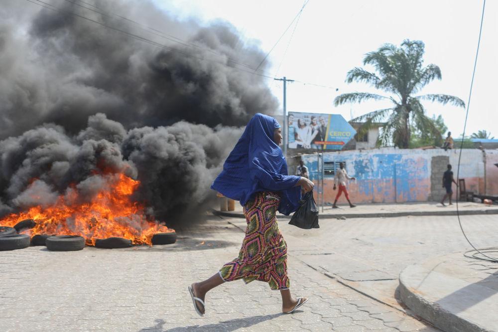 امرأة تجري بالقرب من العجلات المشتعلة أثناء الاحتجاجات في بينين، 9 مارس/ آذار 2018