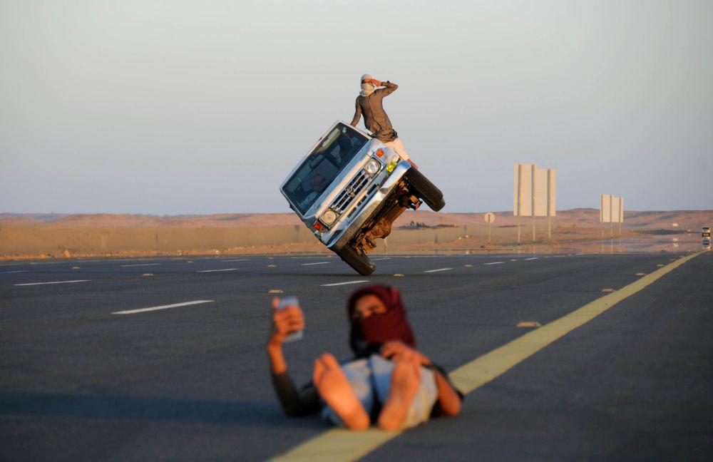 شاب يلتقط صورة سيلفي على خلفية شابين سعوديين يقودان سيارة على عجلتين فقط في تبوك، السعودية 11 مارس/ آذار 2018
