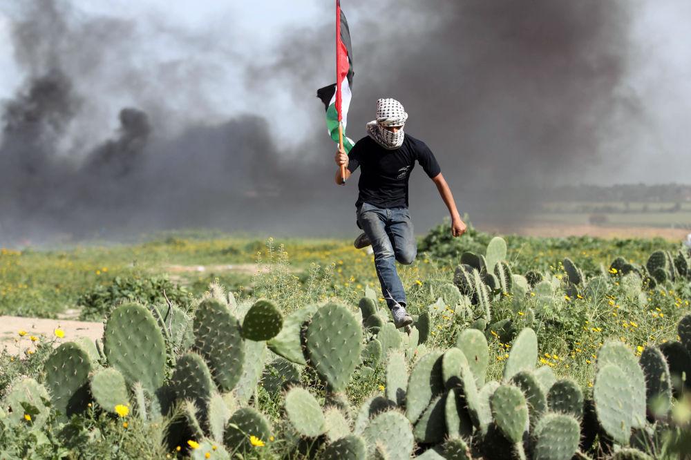 شاب فلسطيني يعبر حقلا من الصبار أثناء الاشتباكات مع القوات الإسرائيلية بالقرب من خان يونس، على الحدود قطاع غزة وإسرائيل، 9 مارس/ آذار 2018
