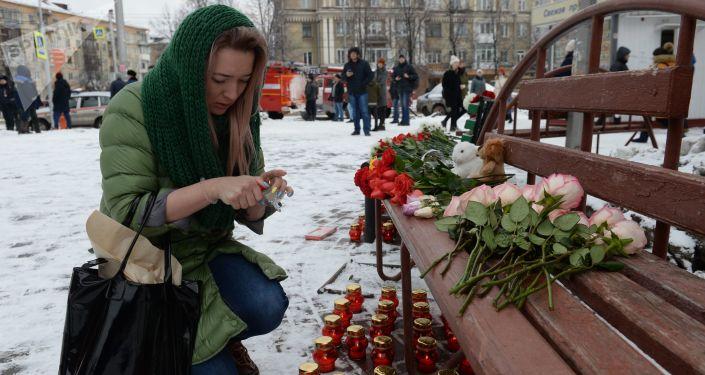 امرأة تشعل شمعة بالقرب من الحادث في كيميروفو